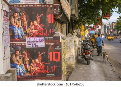 TAMIL NADU, INDIA - FEBRUARY 09, 2016:  Film or movie poster beside  narrow foot paths and stray dogs  running behind pedestrians in Coimbatore.