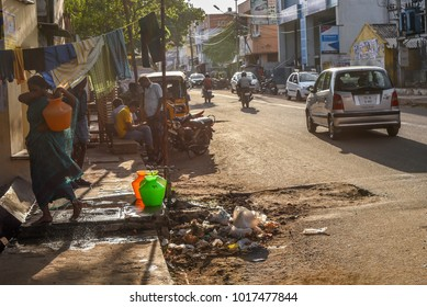 TAMILNADU, INDIA - FEBRUARY 09, 2016:  An Indian women collecting and carrying water in plastic pots in a slum in the outskirts of city of Coimbatore.