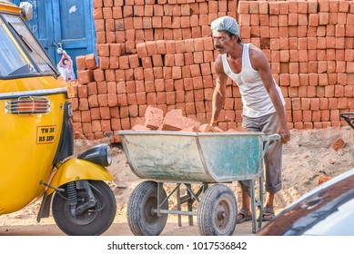 TAMILNADU, INDIA - FEBRUARY 09, 2016:  Indian man or worker carrying bricks in a construction site in Coimbatore.