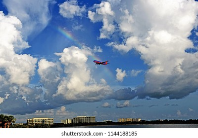 Tampa, FL, July 2018 - A Southwest Airlines Boeing 737 is approaching Tampa International Airport in beautiful blue skies, white clouds and a rainbow whilst flying over Tampa Bay