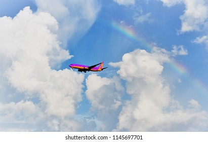 Tampa, FL, July 2018 - A Southwest Airlines twin engine jet is approaching beautiful Tampa International airport amidst building thunderstorm clouds and a rainbow in dark blue skies