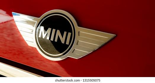 Tampa, FL, USA - 2/17/2019: Mini Logo/Emblem from red Mini Cooper car/automobile.  Closeup. Clean, wide crop.