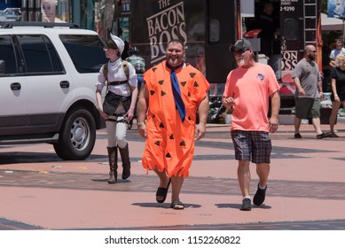 Tampa, Florida / USA - August 4, 2018: Two guys, one dressed in a Fred Flintstone costume walking outside the Tampa Convention Center during Comic Con