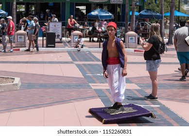 Tampa, Florida / USA - August 4, 2018: Young boy dressed as Aladdin and riding on a magic carpet via a motorized skateboard  outside the Tampa Convention Center during Comic Con