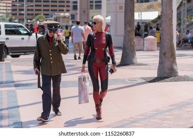 Tampa, Florida / USA - August 4, 2018: Woman in Deadpool Costume and a Young Man in a military uniform walking outside the Tampa Convention Center during Comic Con