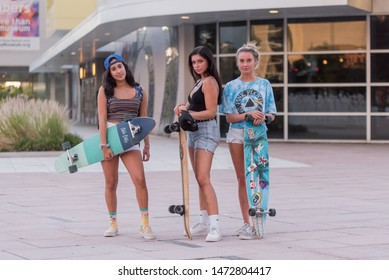 Tampa, Florida / USA - August 6, 2019: Portrait of three Teenage Girls Holding There Ten Toes Long Boards at Curtis Hixon Waterfront Park in Tampa, FL