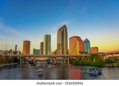 Tampa, Florida, USA - January 12, 2020 : The skyline of downtown Tampa at sunset with tourist boats on the Hillsborough river.