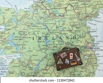 Tampa, Florida / USA - July 8th 2018; vintage leather suitcase cheerfully decorated with flags and travel souvenir stickers lying on a map of Ireland next to Dublin and the North Sea