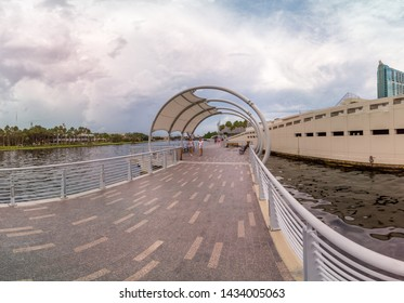 Tampa, Florida / USA - June 8, 2019: Panoramic View of Two Woman Walking on a Cloudy Day on the Tampa Riverwalk