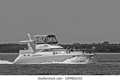 TAMPA, FLORIDA/USA - April 1, 2018: A large Sea Ray motor yacht up on plane while cruising through the waterways of Florida.