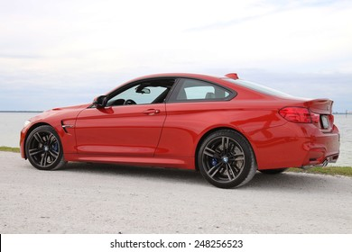 TAMPA, FLORIDA/USA - JANUARY 18 2015: The brand new 2015 BMW M4 parked near a beach in Tampa, FL. This Sakhir Orange M4 has a 6 cylinder twin turbo engine as well as the upgraded 19 inch black wheels.