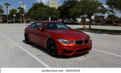 TAMPA, FLORIDA/USA - July 10 2015: A new 2015 BMW M4 parked in a Publix parking lot in Tampa, FL. This Sakhir Orange M4 has a 6 cylinder twin turbo engine as well as the upgraded 19 inch black wheels.