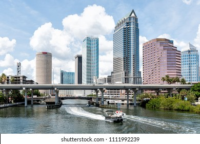 Tampa, USA - April 27, 2018: Downtown city in Florida with bridges, highway, boat yacht, skyscrapers office modern buildings with signs for Wells Fargo, NBC, Sykes, and Bank of America