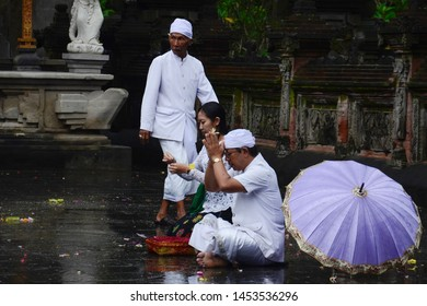 Tampaksiring, Bali - December 25, 2017. Showing traditional Balinese male and female are praying at Tirta Empul Hindu Temple.