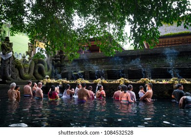 Tampaksiring, Bali / Indonesia - December 26 2017: Balinese people doing a ceremonial ritual in the baths of the Tirta Empul Temple