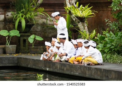 Tampaksiring, Bali / Indonesia - March 17 2017: Balinese kids enjoying snacks after attending a ceremony in the Pura Tirta Empul (Balinese Temple) in traditional dresses in Bali, Indonesia.