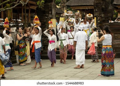 Tampaksiring, Bali / Indonesia - March 17 2017: Balinese women carrying offering to the God on their heads, taking out a procession during a Hindu ceremony in Pura Tirta Empul (a Hindu temple in Bali)