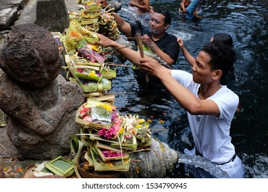 Tampaksiring, Bali/Indonesia - Jan 29th, 2014: Indonesian people  pray and enjoy bathing  in the holy water pool at Tirta Empul Temple, Bali