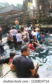 Tampaksiring, Bali/Indonesia - May 24th, 2014: Balinese Hindu pilgrims and foreign tourists enjoy bathing in the holy water pool at Tirta Empul Temple, Bali