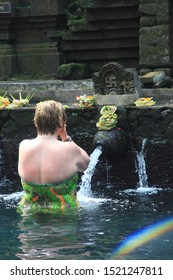 Tampaksiring, Bali/Indonesia - May 24th, 2014: A foreign tourist lady enjoy bathing in the holy water pool at Tirta Empul Temple, Bali
