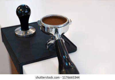 Tamped and compacted coffee grounds in a silver portafilter on a black tamper mat