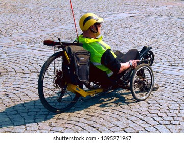 Tampere, Finland - April 25, 2019: Man with helmet and safety vest on recumbent bicycle on a cobbelstone road.