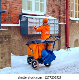 Tampere, Finland - January 3 2019: Portrait of postman (postwoman, woman letter carrier) with trolley in the street sharing mail in boxes