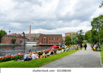 TAMPERE, FINLAND - JULY 18, 2015: People having picnic in the riverside.