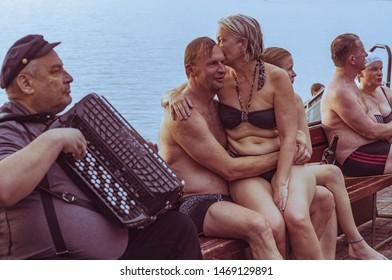 Tampere, Finland - June 23, 2017: Finnish people enjoying public sauna next to lake, man playing accordion celebrating midsummer.