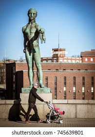 Tampere, Finland - March 7 2013: Person with a stroller in front of a statue on Hameensilta Bridge, Tampere City.