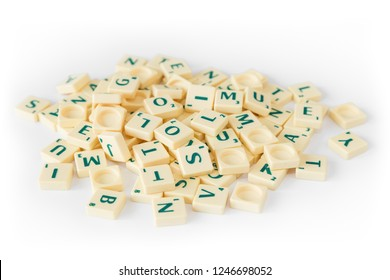 Tampere, Finland - November 21, 2018: Pile of random Scrabble game letter tiles with score value mixed up, isolated on white background.