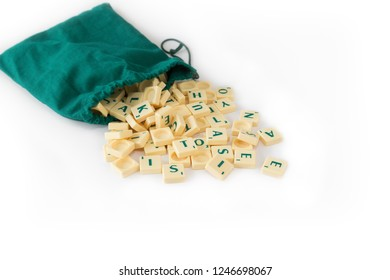Tampere, Finland - November 21, 2018: Random Scrabble game letter tiles with score value coming out of their green drawstring bag, isolated on white background.