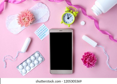 Tampon, feminine, sanitary pads for critical days, feminine calendar, alarm clock, pain pills during menstruation and a pink flower on a pink background. Tracking the menstrual cycle and ovulation.