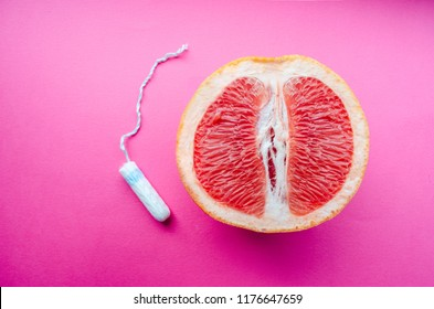 tampon and grapefruit on a pink background. Concept Vagina symbol and menstruation