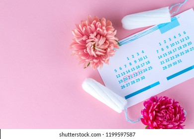 Tampons for menstruation, women's calendar and flowers on a pink background. Hygiene care during critical days. Regular menstrual cycle. Copy space