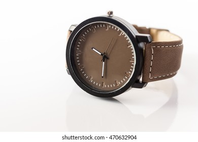Tan brown wristwatch on plain background