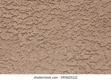 A tan colored abstract stucco background. - Shutterstock ID 1903625122