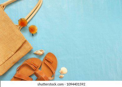 Tan colored leather sandals, canvas bag and golden sunglasses on blue background. Summer beach accessories, top view point, flat lay.