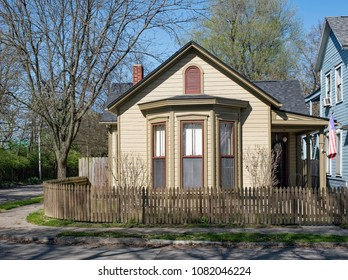 Tan Corner Cottage with Natural Wooden Picket Fence
