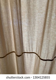 Tan curtain with brown stripe with folds, puckers and gathers