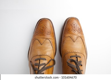 Tan fashionable male brogue shoes on white background view from above