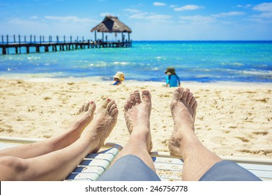 Tan Feet of a couple on lounge chairs enjoying a beach vacation while watching their kids play in the sand
