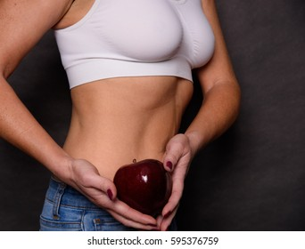 A Tan Fit Woman Holding A Red Apple