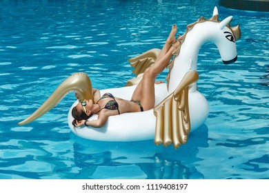 Tan girl lies on inflatable mattress white unicorn in the pool