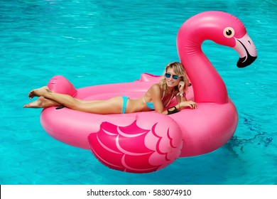 Tan girl sits on inflatable mattress flamingos in the pool