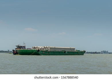 Tan Phong, Mekong Delta, Vietnam - March 13, 2019: Large green pontoon filled with gray large concrete beams. Tugboat along under blue sky, brown-greenish water. Cruise ship on horizon.