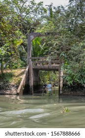Tan Phong, Mekong Delta, Vietnam - March 13, 2019: Small concrete bridge over ditch emptying into canal engulfed by green tree foliage. Small blue motorboat along shore.