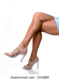 Tan sexy legs in heels isolated on a white background.