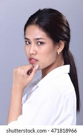 Tan skin asia girl in white shirt over grey background