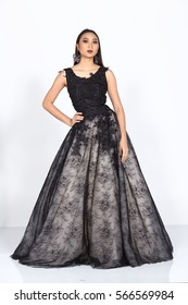 Tan Skin Woman Model in Black Long evening Gown ball dress with open arms hands, studio lighting gray background